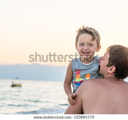 Happy family. Young beautiful father and his smiling son baby boy having fun on the beach of the sea, ocean. Positive human emotions, feelings, joy, kissing.Funny cute child making summer vacations.