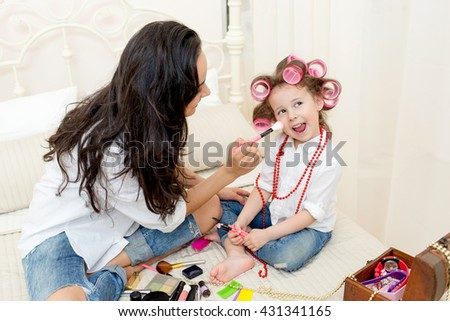 Happy family. Young beautiful mother does makeup her pretty daughter on the bed in the bedroom . Daughter with curlers on her head laughing - stock photo