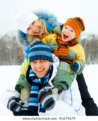 happy family, young couple and their son spending time outdoor in winter - stock photo