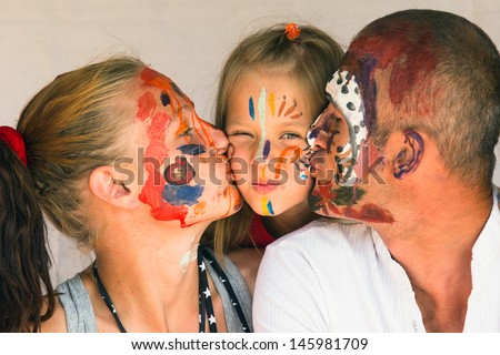 Happy family - young couple kissing baby daughter, after playing with paints. - stock photo