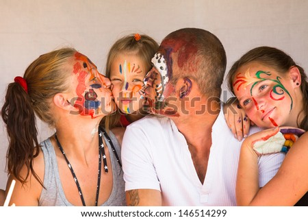Happy family - young couple kissing younger baby daughter, after playing with paints - stock photo