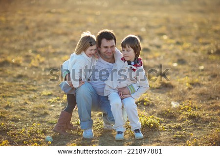 Happy family: young father with his little children walking in the field in summer morning. Strong healthy daddy holding his daughter and his son in a lap .  - stock photo