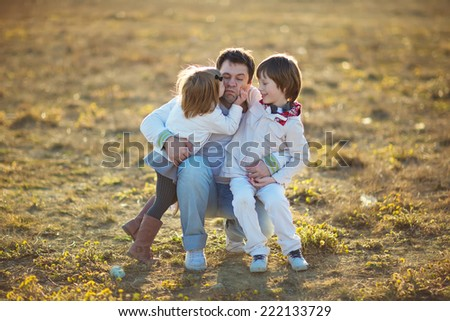 Happy family: young father with his little children walking in the field in summer morning. Strong healthy daddy hugging his daughter and his son.  - stock photo