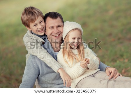 Happy family: young father with his little children walking in the field on a warm autumn day. A portrait of a strong healthy daddy with his daughter and his son.  - stock photo