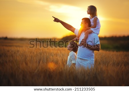 Happy family: young father with his little children walking in the wheat field at summer sunset. Girl is sitting on her daddy's shoulders and the man is pointing his daughter and son to something.  - stock photo