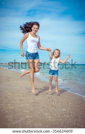 Happy family. Young happy beautiful  mother and her daughter having fun on the beach. Positive human emotions, feelings, emotions. - stock photo