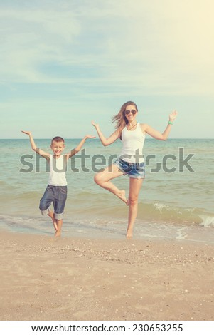 Happy family. Young happy beautiful  mother and her son doing yoga on coast of sea on beach.   - stock photo