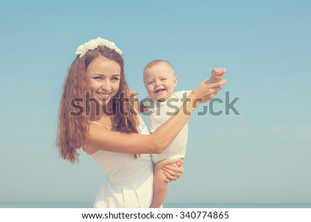 Happy family. Young happy beautiful  mother and her son having fun on the beach. Positive human emotions, feelings.