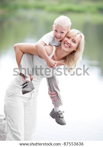 happy  family; young mother and her five year old son spending time outdoor on a summer day (focus on the woman) - stock photo
