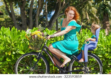 Happy family - young mother bicycling and have fun with little daughter in baby bike seat Active parents, people outdoor activity and exercises with children on summer vacation in tropical island Bali - stock photo