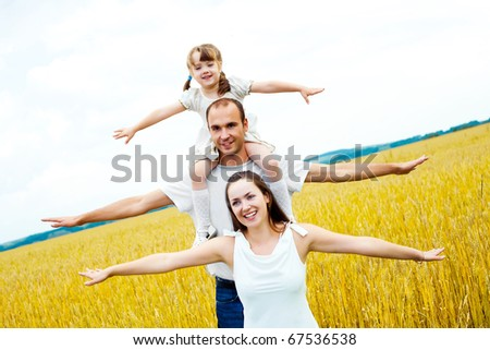 happy family; young mother, father and their daughter having fun at the wheat field - stock photo