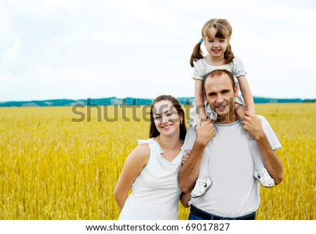 happy family; young mother, father and their daughter having fun at the wheat field (focus on the woman) - stock photo