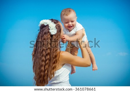 Happy family. Young mother throws up baby in the sky, on sunny day on the beach. Positive human emotions, feelings.