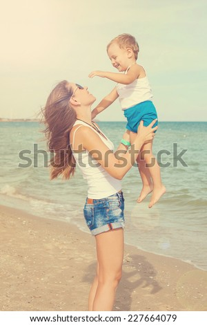 Happy family. Young mother throws up baby in the sky, on sunny day. Portrait mom and little son on the beach. Positive human emotions, feelings, joy.