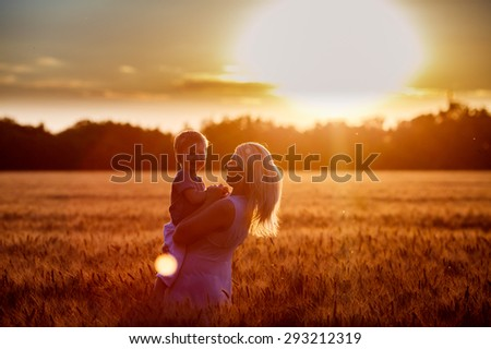 Happy family. Young mother throws up baby in the sky, on sunny day. Portrait mother and little son on  the  Field. Positive human emotions, feelings, emotions.Toned in warm colors - stock photo