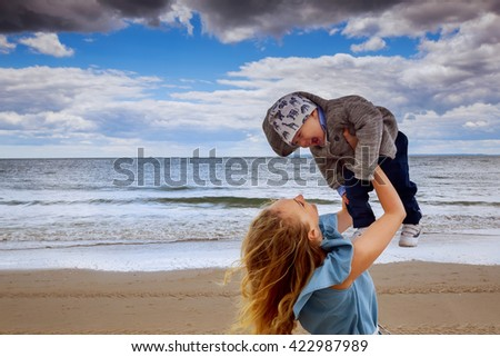 Happy family. Young mother throws up baby in the sky, on sunny day.  Positive human emotions, feelings, emotions. - stock photo