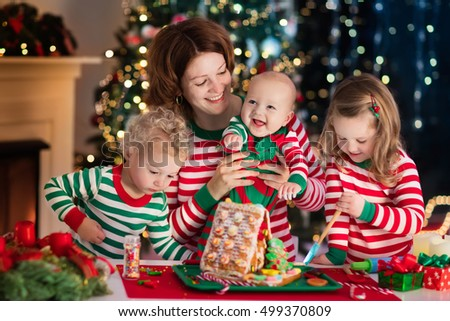 Happy family, young mother with baby, little boy and girl making gingerbread house at fireplace in decorated living room with Christmas tree. Baking and cooking with children for Xmas at home.