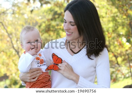 Happy family - young mother with her adorable baby boy son in a park, suitable for a variety of family, parenting and seasonal themes - stock photo