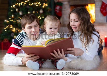 Happy family - young parents reading a book to child son near Christmas tree