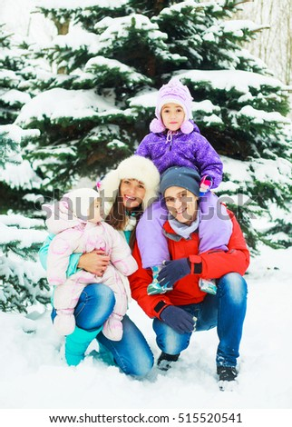 happy fanmily with two kids in the winter park outdoor