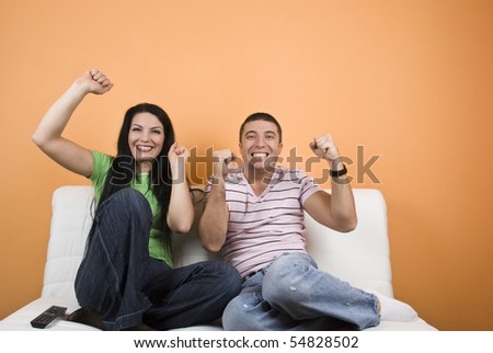 Happy fans couple watching TV their favorite sport team - stock photo