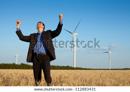 happy farmer (businessman) standing in wheat field over wind turbines background and holding hands up