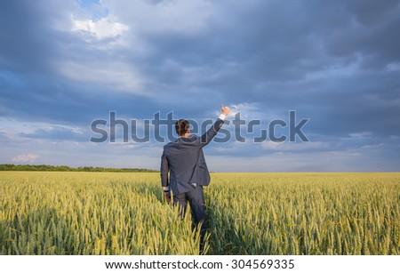 happy farmer, businessman, standing in wheat field over wind turbines background with his hands up and thumbs up