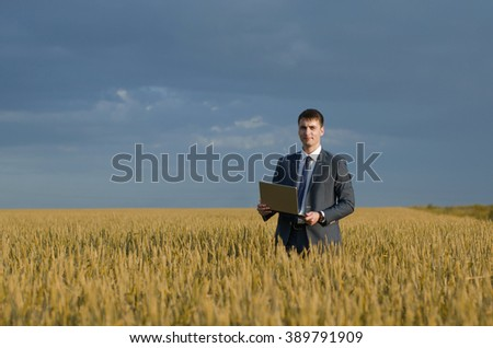 happy farmer, businessman, standing in wheat field with his laptop