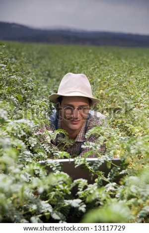 happy farmer in the fields with a laptop computer - stock photo