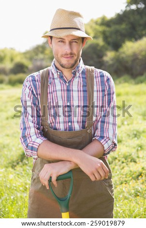 Happy farmer smiling at camera on a sunny day - stock photo