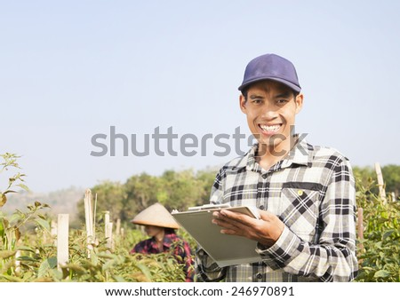 Happy farmers man holding notepad on chili peppers garden - stock photo