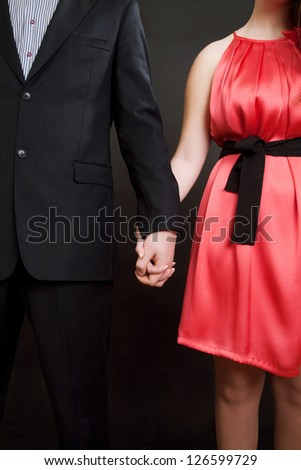 Happy fashion couple holding by hands at valentines day - stock photo