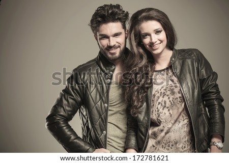 happy fashion couple in leather jackets smiling to the camera in studio - stock photo