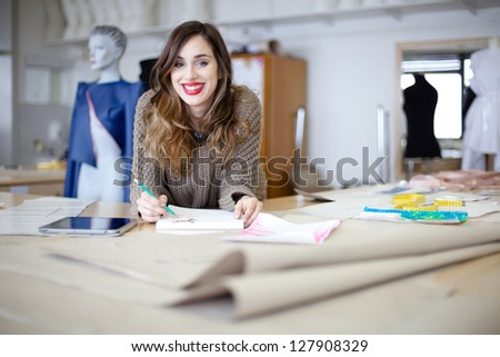 Happy fashion designer working on her designs in the studio - stock photo