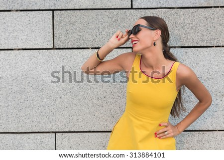 Happy fashion girl keeping her sunglasses and smiling. Pretty lady in yellow dress posing with her hand on hip over brick wall. - stock photo