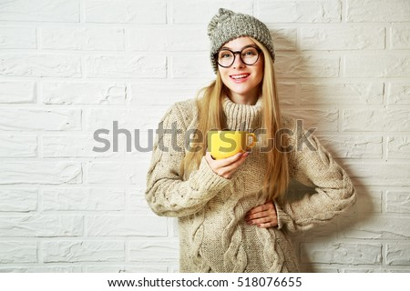 Happy Fashion Hipster Girl in Knitted Sweater and Beanie Hat with a Mug in Hands. Smiling Nice Woman at White Brick Wall Background. Winter or Autumn Warming Up Concept. Toned Photo with Copy Space.