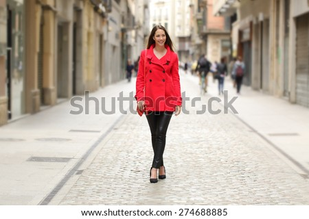 Happy fashion woman in red walking on a city street in winter - stock photo
