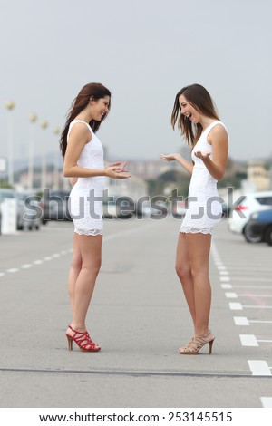 Happy fashion women wearing the same dress and looking amazed - stock photo