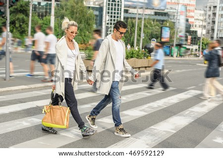 Happy fashionable couple crossing road at pedestrian zebra crossing in the city
