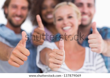 Happy fashionable group giving thumbs up on white background - stock photo