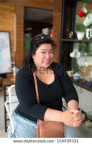 Happy fat business woman in coffee shop