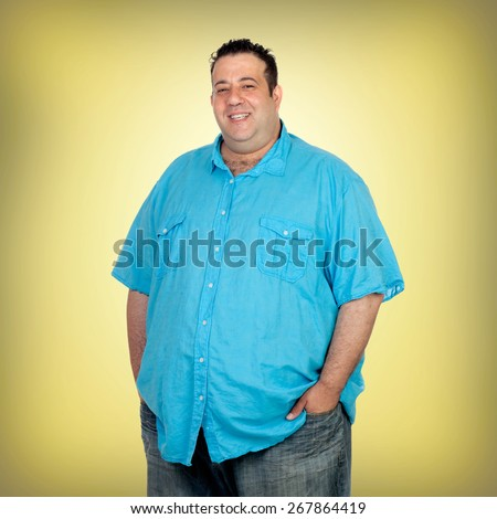 Happy fat man with blue shirt and a yellow background - stock photo