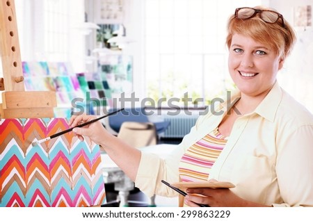 Happy fat woman painting at home, smiling, looking at camera. - stock photo