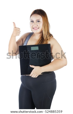 Happy fat woman showing ok gesture with her thumb while holding weight scale, isolated on white background