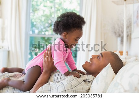 Happy father and baby girl lying on bed together at home in the bedroom - stock photo