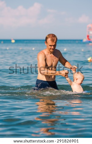 Happy father and baby having fun in the sea, exercising in water