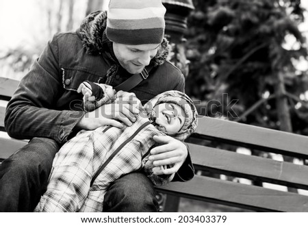 happy father and baby son playing outdoors (black and white) - stock photo