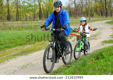 Happy father and child on bikes, family cycling outdoors  - stock photo
