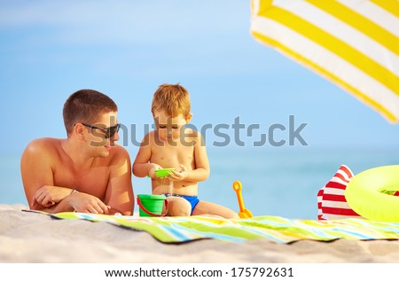happy father and child playing in sand on the beach - stock photo