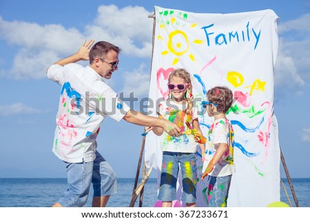 Happy father and children playing with paint on the beach at the day time. Concept of friendly family. - stock photo